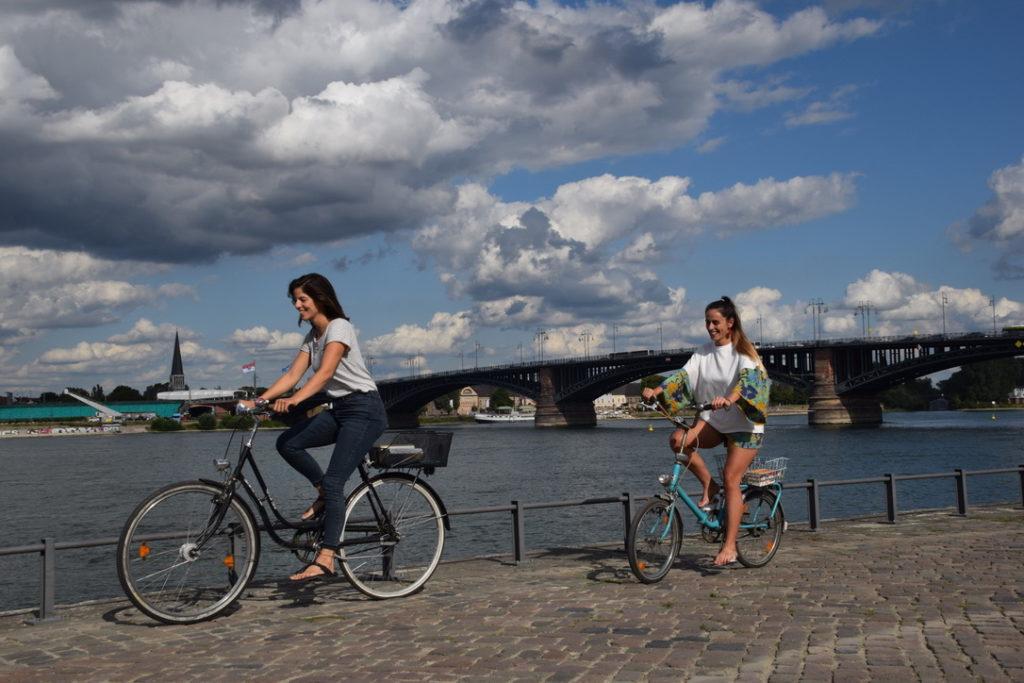 Zwei Freundinnen auf dem Fahrrad am Rhein in Mainz